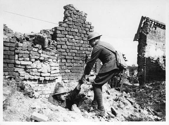 Jeden żołnierz pomaga drugiemy wyjśc z wykopu lub domu